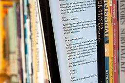 Numa prateleira, e-reader entre livros impressos. Foto: Maximilian Schönherr