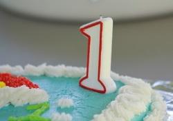 Detalhe de bolo de aniversário azul com vela de 1 ano no canto. Fonte: Pixabay